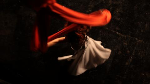 woman in white dress spins red silks